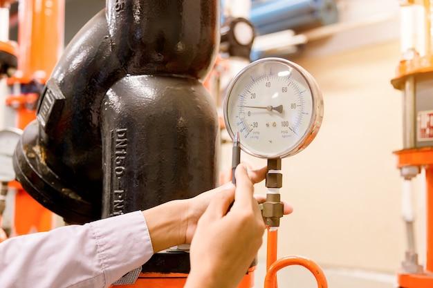 Engineer checking pressure gauge.