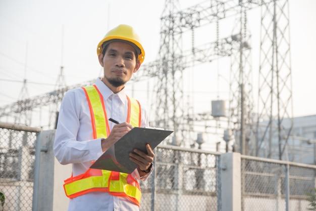 Инженер проверяет систему безопасности на электростанции, высоковольтный завод