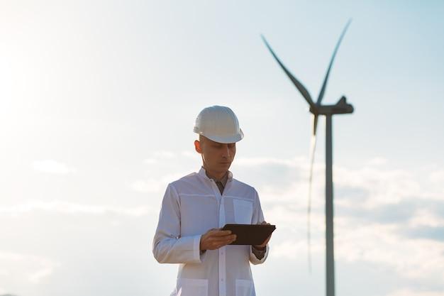エンジニアはタブレットで風力タービンシステムをチェックします。