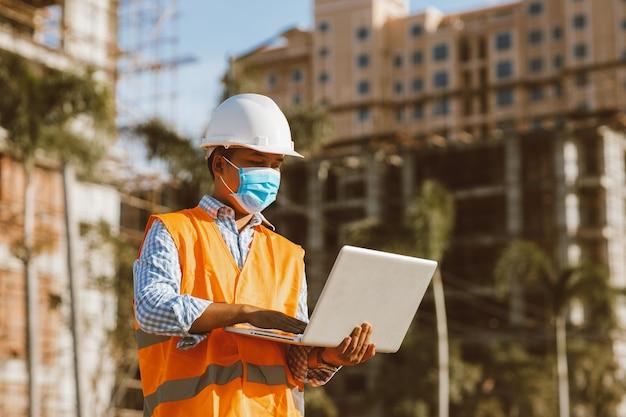 Инженер-строитель в защитной маске от распространения заболеваний covid 19 во время осмотра строительной площадки с ноутбуком. концепция безопасности