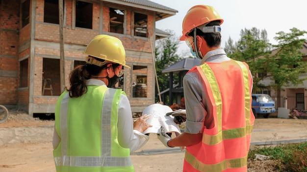 Команда инженеров-подрядчиков встречается с промышленным проектом плана безопасности труда и проверяет дизайн на строительной площадке.