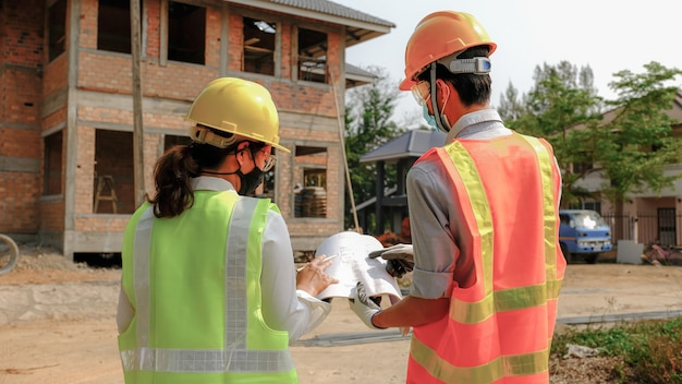 Engineer contractor team meeting work safety plan industry project and check design at the construction building site.