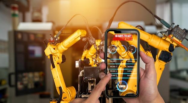 Инженер управляет роботизированным оружием с помощью технологии индустрии дополненной реальности Premium Фотографии