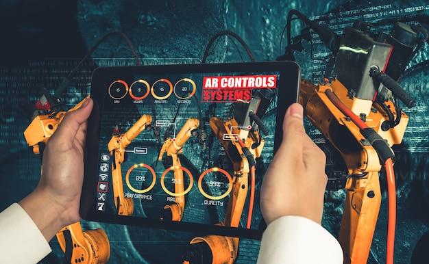 Инженер управляет роботизированным оружием с помощью технологии индустрии дополненной реальности
