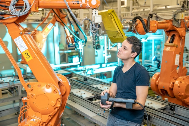 Engineer controls using remote control of industrial robot in factory. automatic welding and gluing using automation and robotic arms