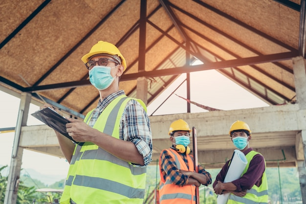 Engineer corporate workers wearing protective masks to prevent dust and covid 19 working together at construction site construction site,coronavirus has turned into a global emergency.