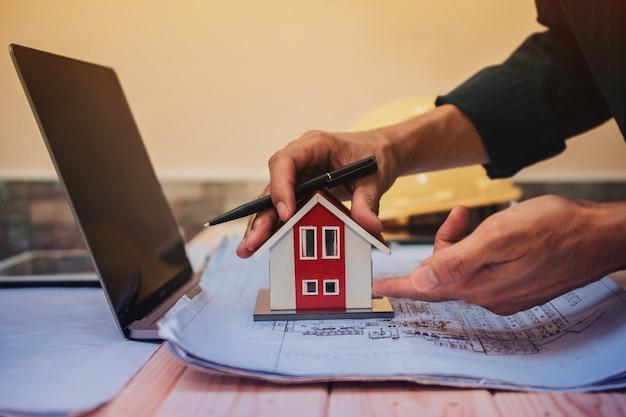 Инженер проектирует проект строительства дома по плану компьютерного ноутбука