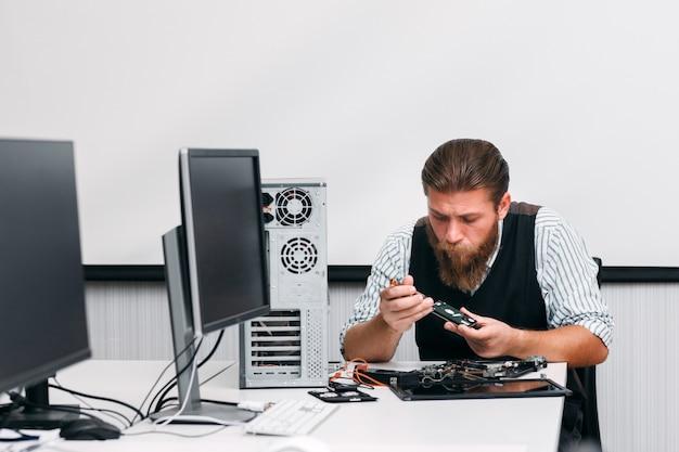 Cpuのdvdドライブ部分を分解するエンジニア。修理店でのcd-romの改修。電子リフォーム、ビジネス、技術の概念