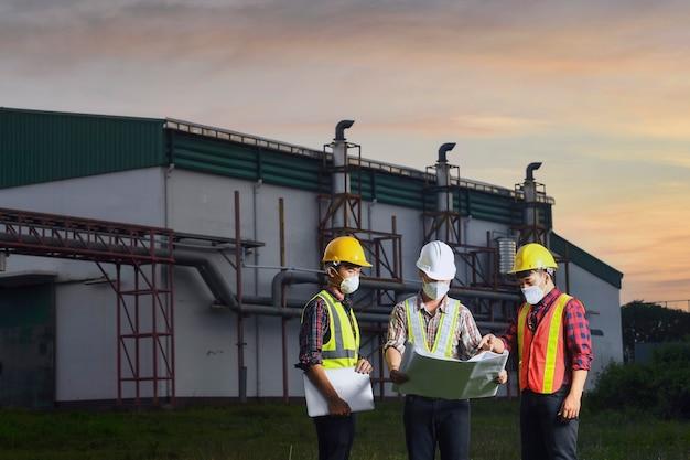 Инженер вместе с ним обсуждает техническую документацию на территории современного завода. инженеры работают на территории электростанции.