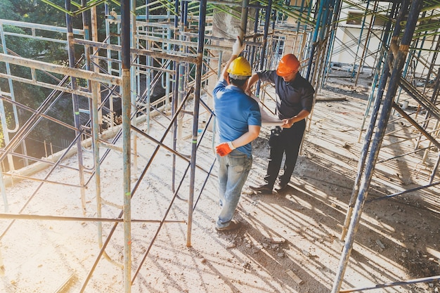 Engineer discussing with foreman about project in construction site