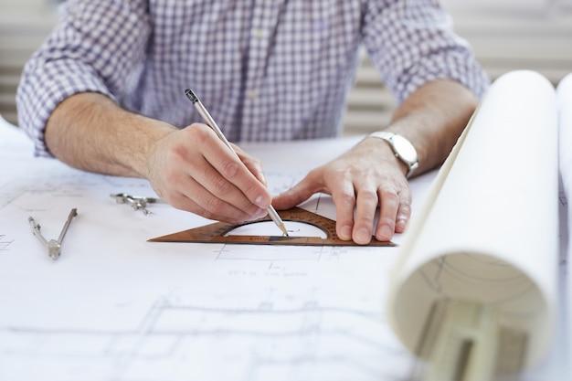 Инженер рисует планы на рабочем месте