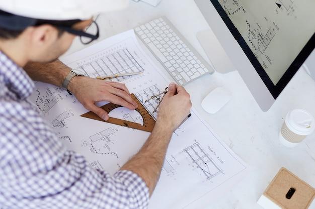 Инженер рисует планы высокого угла