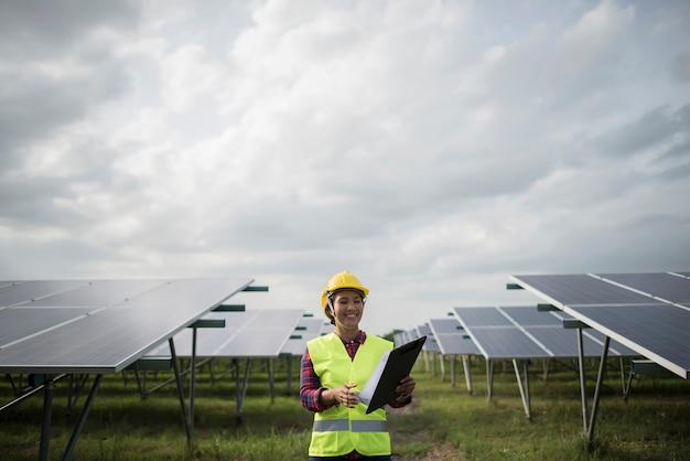エンジニア電気女性のチェックと太陽電池のメンテナンス。