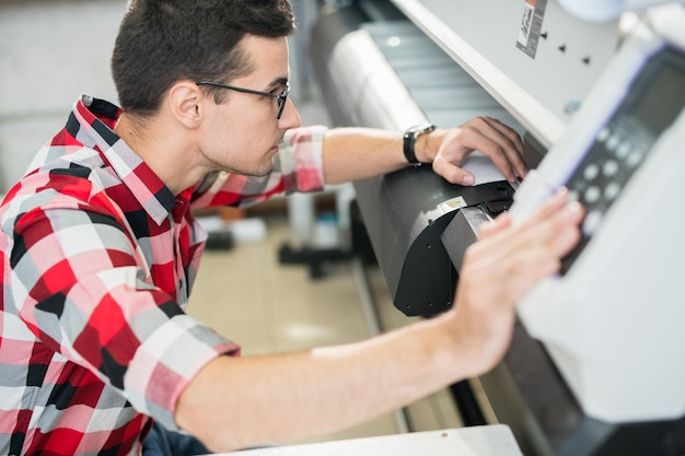 Engineer examining wide format printer