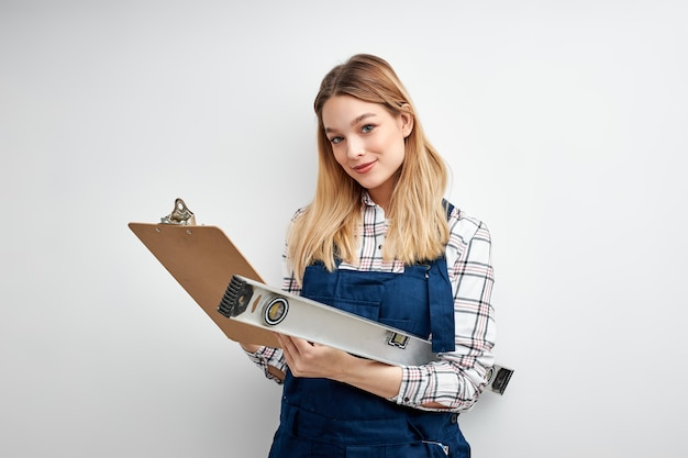 Engineer female in builder uniform smile holds clipboardand level tool