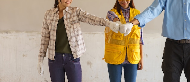 Engineer and female workers are putting hand together