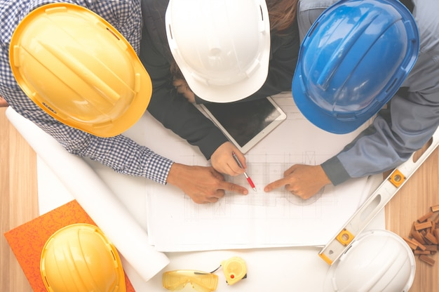 Engineer and foreman wearing safety helmet are meeting at site outdoor and pointing to drawing paper
