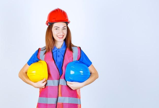 파란색과 노란색 헬멧을 들고 선택을 하는 제복을 입은 엔지니어 소녀.