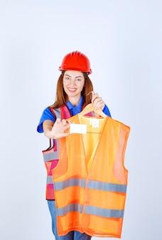 Девушка-инженер в военной форме преподносит коллеге кусок защитной куртки и представляет свою визитную карточку.