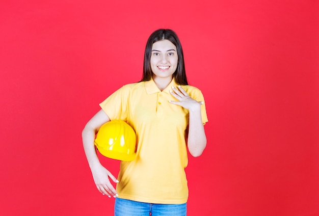 Девушка-инженер в желтом дресс-коде держит желтый защитный шлем и чувствует себя позитивно и счастливой.