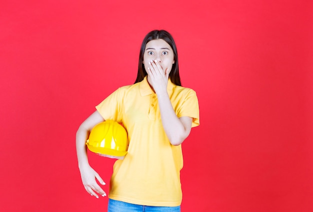 Девушка-инженер в желтом дресс-коде держит желтый защитный шлем и выглядит напуганной и напуганной.