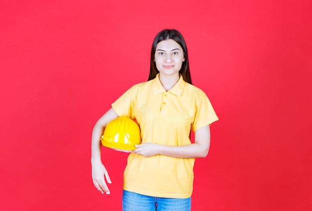 Девушка-инженер в желтом дресс-коде держит желтый защитный шлем