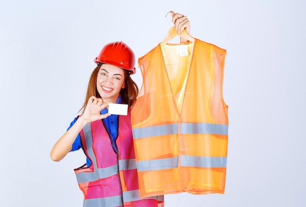 Ragazza ingegnere in uniforme che presenta un pezzo di giubbotto di sicurezza al collega e presenta il suo biglietto da visita.