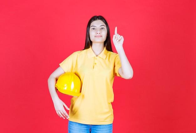 Ragazza ingegnere in codice di abbigliamento giallo che tiene un casco di sicurezza giallo e mostra da qualche parte