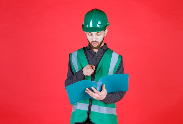 Engineer in green uniform and helmet holding a blue folder, reading and making corrections.
