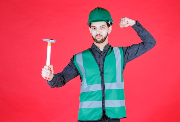 Ingegnere in uniforme verde e casco che tiene un'ascia di legno e mostra un segno positivo con la mano.
