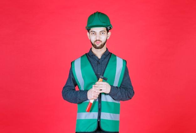 Ingegnere in uniforme verde e casco che tiene un'ascia di legno.