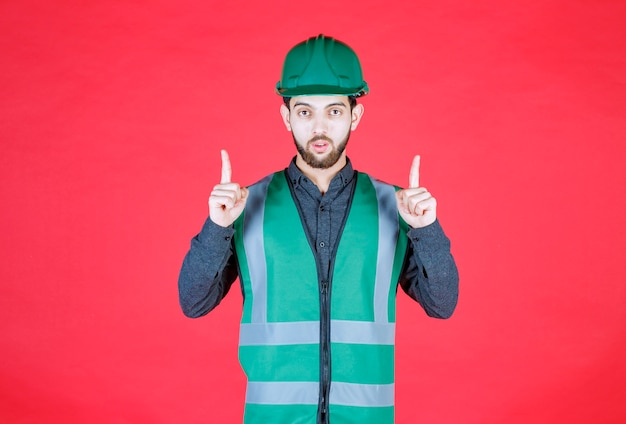 Engineer in green uniform and helmet pointing above.