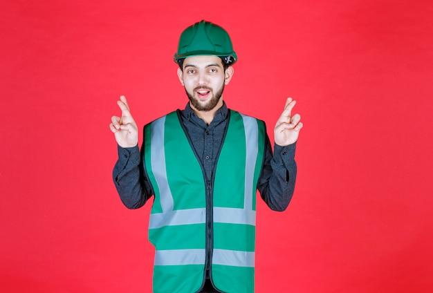 Ingegnere in uniforme verde e casco che mostra il segno della croce del dito.