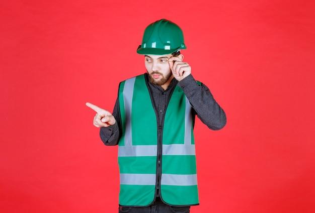 Ingegnere in uniforme verde e casco che mostra il lato sinistro.