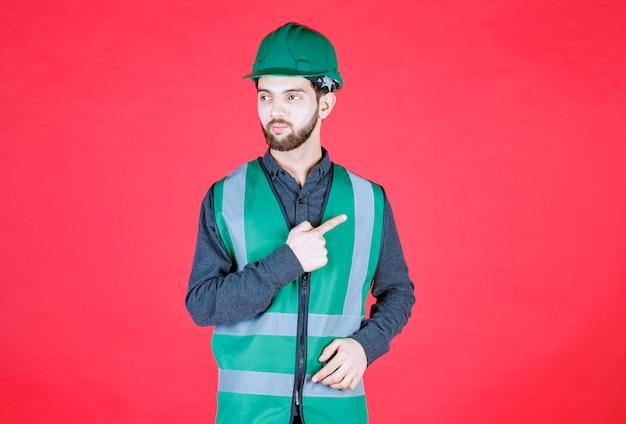 Ingegnere in uniforme verde e casco che mostra il lato destro.