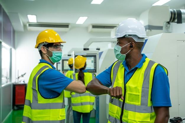 工場でぶつかる肘を挨拶するエンジニア
