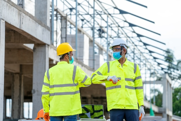 Engineer greeting with elbows at building construction site