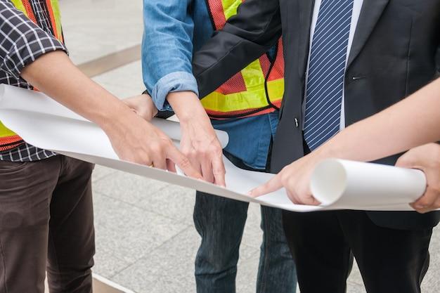 リーダーのビジネスマンと一緒に紙を指すエンジニアグループ