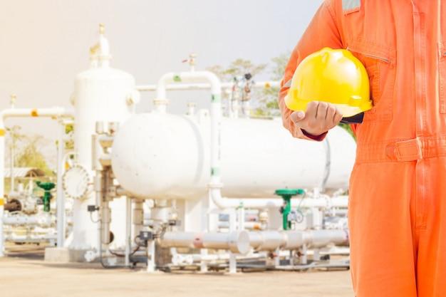 Инженер рука желтого шлема для рабочих против фонового нефтегазового процесса