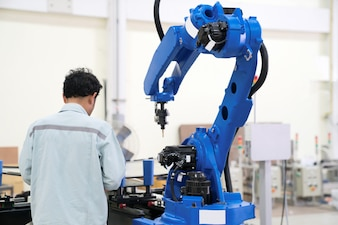Engineer hand using tablet, heavy automation robot arm machine in smart factory industrial