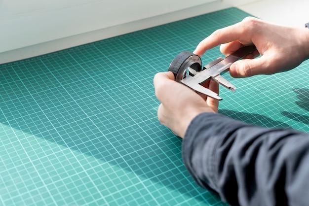 手作業をエンジニアし、キャリパーツールで部品を測定します