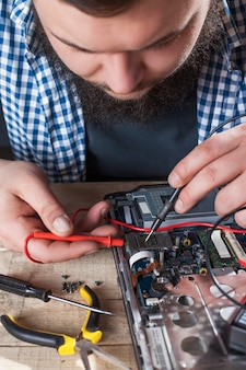Engineer hands diagnostics laptop with multimeter