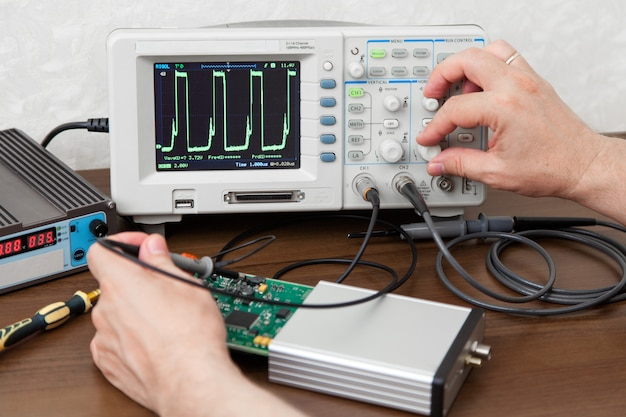 Engineer hands measuring signals on board of electronic device