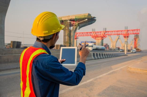 Инженер шлем усердно работает над строительством площадки