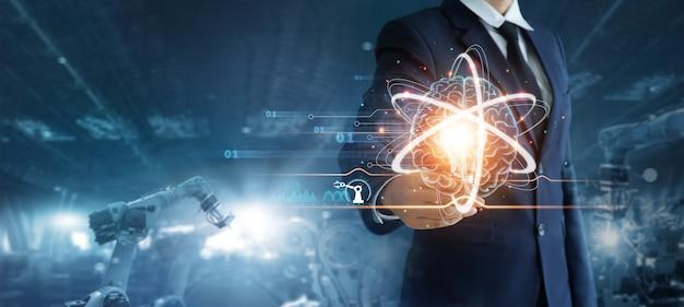 Инженер держит лампочку с мозгом и управляет роботизированным автоматическим оружием, машинным искусственным интеллектом, машинным обучением