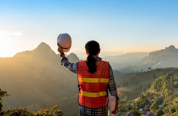 山を見て、白いヘルメットと青写真を保持しているエンジニア