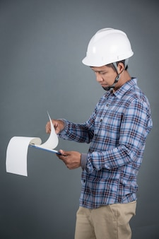 Engineer holding blueprints and reading notes on clipboard while standing on gray background.