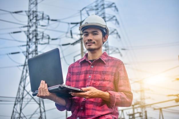 Инженер держит компьютер ноутбук высоковольтной электростанции фон