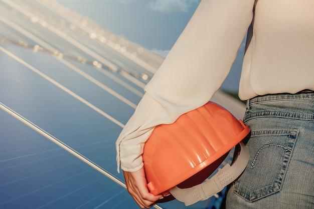 태양 광 발전 패널 배경에 분홍색 건설 헬멧을 들고 엔지니어.