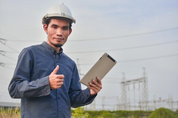 Инженер держит планшет на открытом воздухе высоковольтной системы фон